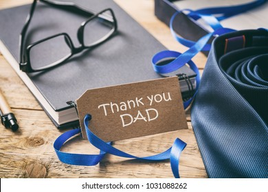 Father's day concept. Blue tie, thank you dad written on the tag, office desk background