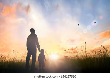 Father's day concept: Father and son standing on meadow autumn sunrise background