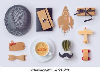 Fathers day concept with hat, coffee cup, notebook and gifts on white background. View from above. Flat lay