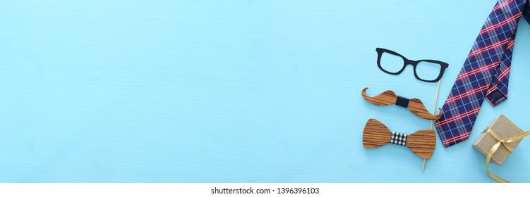 Father's day concept. Hipster glasses, gift box tie and funny moustache over blue wooden background. top view, flat lay