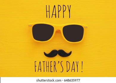 Father's day concept. Hipster yellow sunglasses and funny moustache on wooden background
