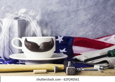 Father's day concept of hot coffee with mustache and tool on the table and american flag