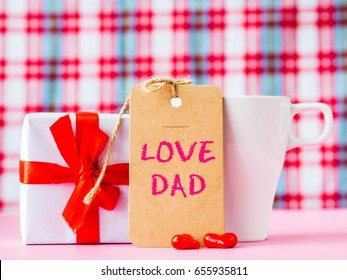 Father's day concept. I LOVE DAD message with coffee cup, two red heart and gift on pink background