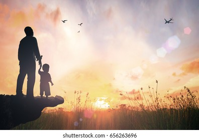 Father's day concept: Silhouette child's hand holding father's finger on mountain autumn sunset background