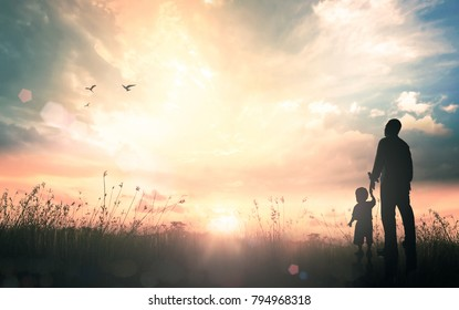 Father's day concept: Silhouettes father and son holding hand in hand on meadow sunset background