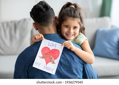 Father's Day Concept. Smiling little girl embracing dad and holding greeting card