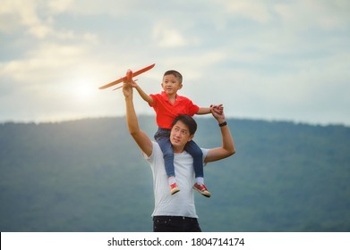 Father's day. dad and baby son playing together outdoors paper plane