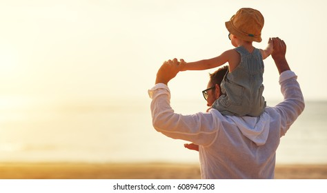 father's day. Dad and baby son playing together outdoors on a summer beach