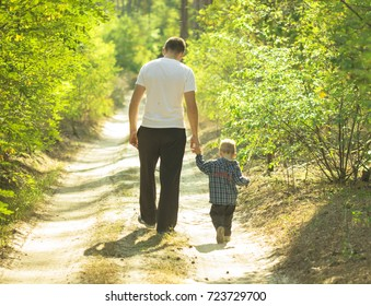 father's day. Dad and baby son playing together outdoors on a summer road