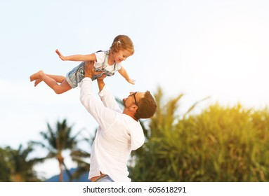 father's day. Dad and child daughter playing together outdoors on a summer beach