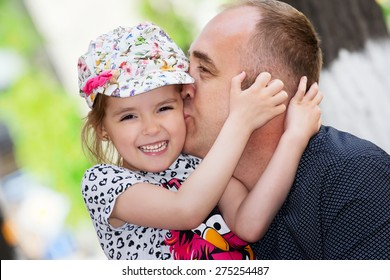 Father's day. Dad kissing his daughter.Happy smiling child with parent. Family portrait.