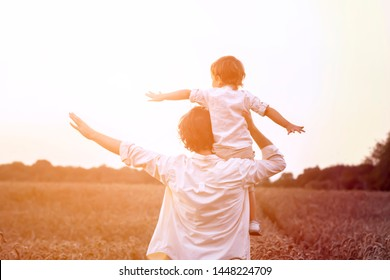 father's day. Dad and son playing together outdoors on a summer. Happy family, father, son at sunset. The concept of organic farming and healthy lifestyle,  happiness and joy