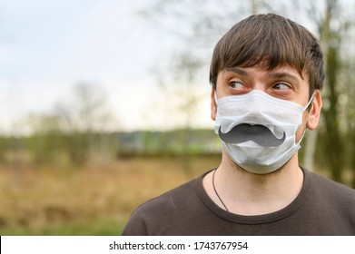 father's day during the covid-19 quarantine concept. portrait a young european man in a protective mask and paper moustache against the background of nature