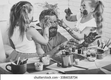 Fathers day and family concept. Daughters and dad smiling with painted hands. Creativity and imagination. Girls drawing on man face skin with colorful paints. Body art and painting.