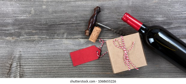 Fathers day gift box with red wine bottle and corkscrew on vintage wooden plank background