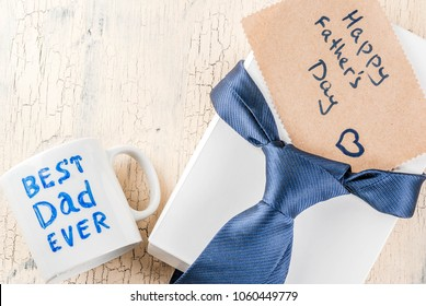 Father's Day gift concept, greeting card background, gift box, tie decoration, mug with inscription Best Dad Ever, notebook, copy space top view