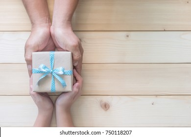 Father's day gift with daughter or son holding dad's hands giving present box with blue  ribbon on wood background to tell I love you dad, I am so thankful and happy fathers day