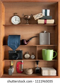 Fathers day gift with label inside a shelving unit with various objects including tools, camera and coffee cup
