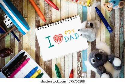 Fathers day greeting card concepts with I love you Dad text and cute dolls. Top view on wooden background.
