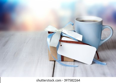 Father's day greeting card mug present gift craft box on wooden table empty space background.Holiday present concept blue color with tag for message.