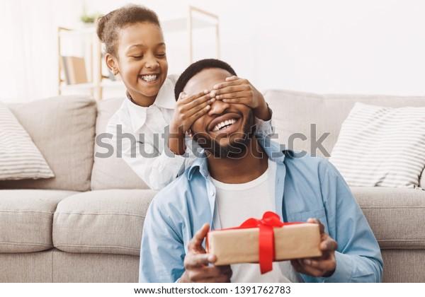 Vaderdag. Gelukkige dochter feliciteert vader en geeft cadeau thuis