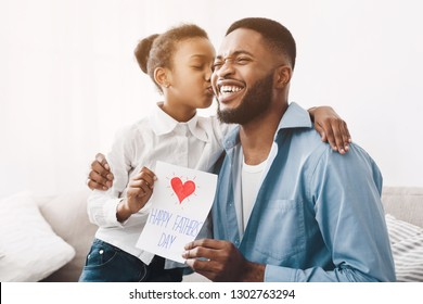 Father's day. Happy daughter kissing dad and giving greeting card