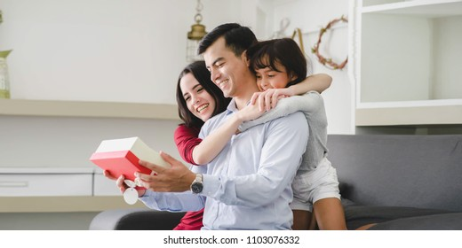 Father's Day and Happy Family Day Asian. Daughter have a Gift for Daddy Celebrate .  Family, Gift, Christmas, Holidays Concept.