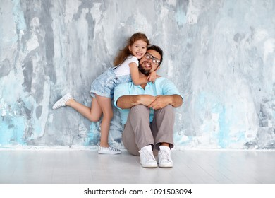 Father's day. Happy family daughter hugging dad and laughs near an empty wall