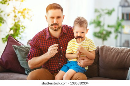 Father's day. Happy funny family son  and dad with mustache   on holiday