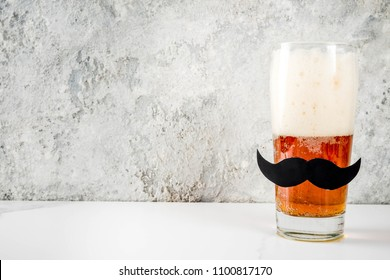 Father's day holiday concept, beer glass with mustache decoration, funny man character, background for greeting card