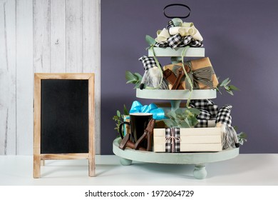 Father's Day or masculine birthday. Chalkboard sign with on-trend farmhouse aesthetic three tiered tray decor filled with gifts, cute black plaid gnomes, and farmhouse style stack of books mockup. - Shutterstock ID 1972064729