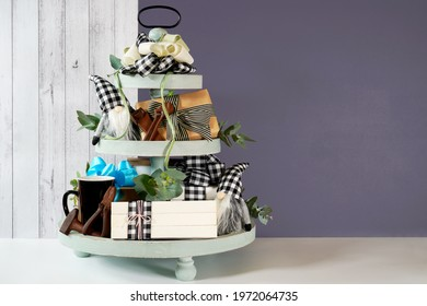 Father's Day or masculine birthday. On-trend farmhouse aesthetic three tiered tray decor filled with gifts, cute black plaid gnomes, and farmhouse style stack of books mockup. Negative copy space. - Shutterstock ID 1972064735