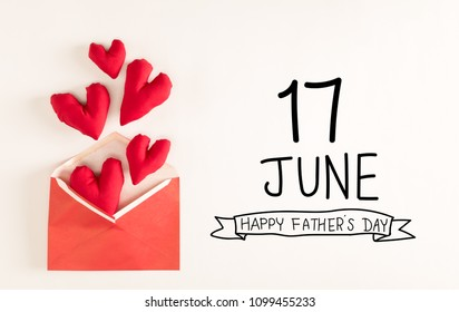 Father's Day message with red heart cushions coming out of an envelope