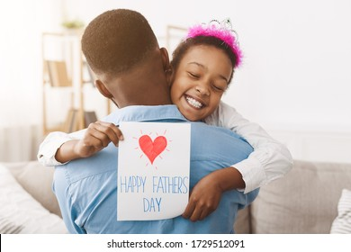Father's day. Pretty afro girl giving dad postcard and hugging him, free space