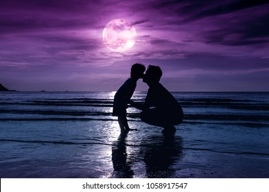 Father's day. Silhouette of loving child kissing her father. Family enjoying and relaxing on beach with full moon on purple sky background in the evening. The moon taken with my own camera.