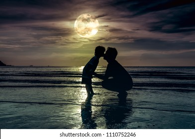 Father's day. Silhouette of loving child kissing her father. Family enjoying and relaxing on beach with full moon on sky background in the evening. The moon taken with my own camera.