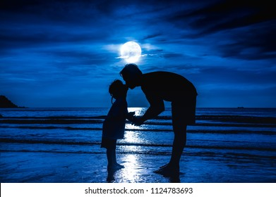 Father's day. Silhouette side view of loving child kissing her father. Family enjoying and relaxing on beach with full moon on blue sky background in the evening. The moon taken with my own camera.