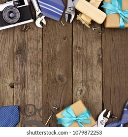 Fathers Day theme double border of gifts, ties and tools on a rustic wood background. Top view with copy space.
