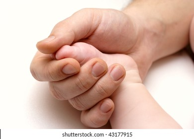 father`s hand holding a baby foot
