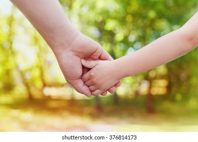 Fathers hand holding his little child in sunny day outdoor, united family and happy childhood concept, beautiful bokeh background