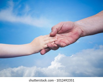 father's hand holding the hand of your child on blue sky background, the concept of the family trust, mutual support