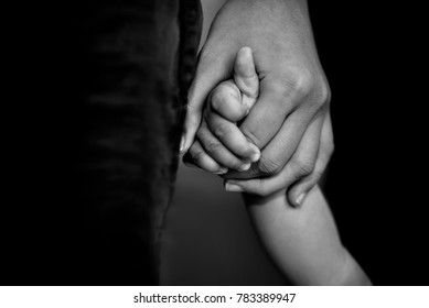 father's hand lead his child son in dark background, trust family concept. selective focus