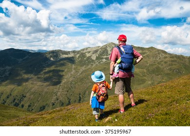 father,son and baby in carrier watching mountain view while hiking in the austrian summer alps