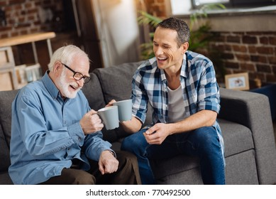 Father-son bonding. Cheerful young man sitting on the sofa next to his father and drinking tea together with him