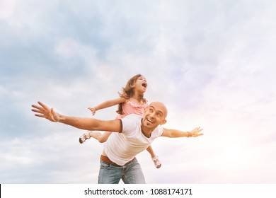 Fathrer and cute daughter sitting on his back and playing like airplane. Bright summer sunny day, happy faces, lovely emotions