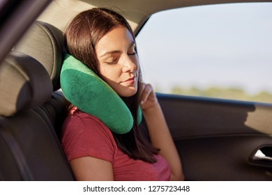 Fatigue brunette woman uses green pillow for travelling in car, has tired look, dressed in casual t shirt, poses in automobile, falls asleep. People, tourism and journey concept. Female enjoys comfort
