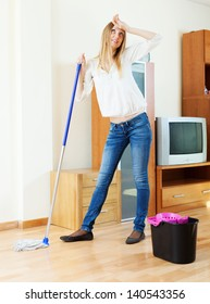 fatigue long-haired girl washing parquet floor with mop at home