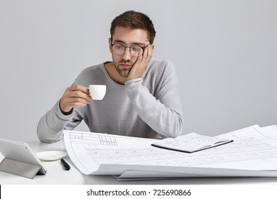 Fatigue man looks tired after work all evening at drawings, looks at cup of espresso or cappucino, feels boredom. Exhausted businessman drinks strong coffee, being sleepy, isolated over grey wall