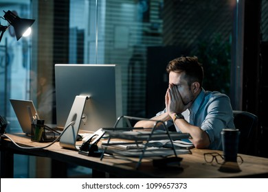 Fatigue man in shirt rubbing face while watching computer totally exhausted working late at night.