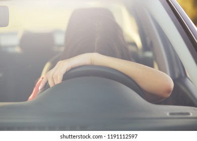 Fatigue sleepless female driver leans on wheel, stops to have rest, poses in car, covered long distance during night, feels tired. View from windshiled. Woman on parking, has nap to drive further